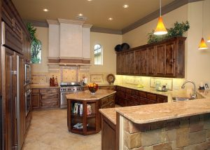 Cordillera Ranch: The dark wood tones of the cabinetry counteract the hard stone surfaces.